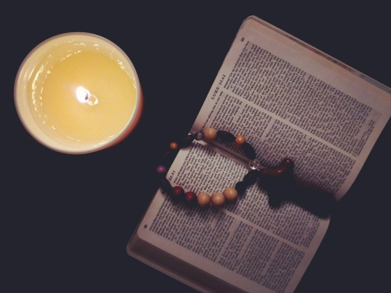 Candle with Bible, cross and prayer beads